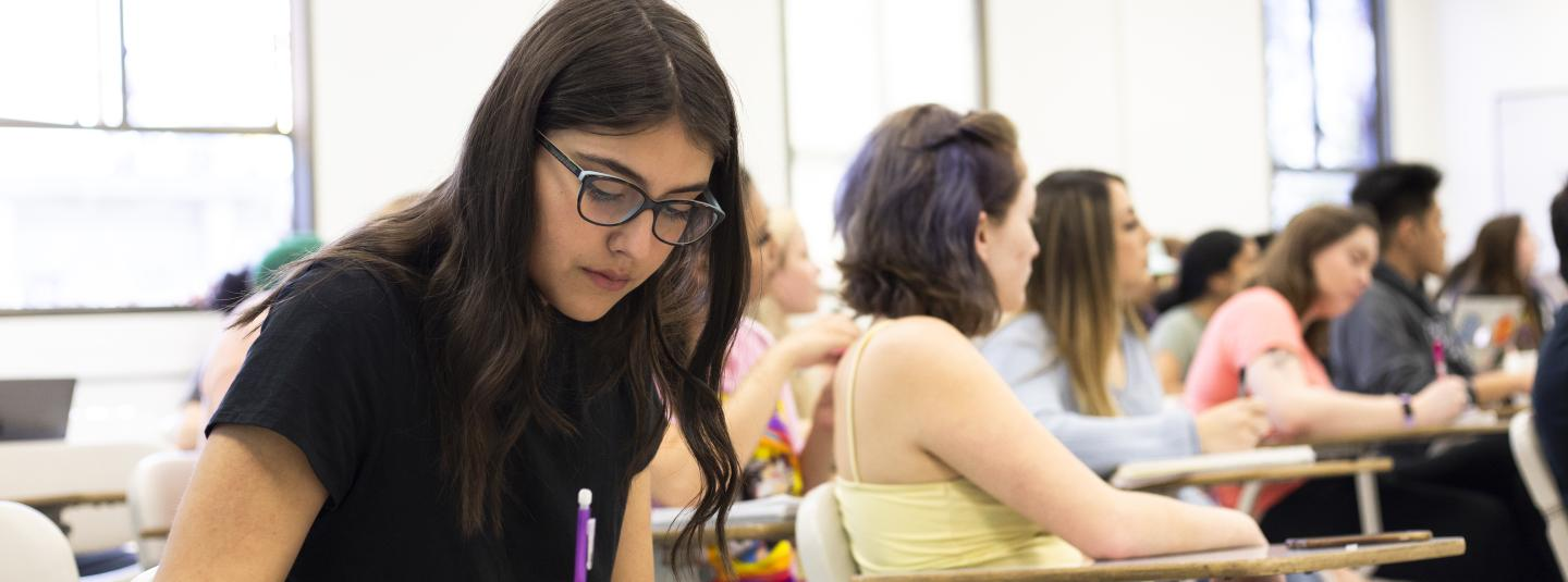 A female student seated in a classroom takes notes.